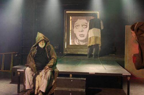 יובל מסקין מתארח בתפקיד הקבצן העיוור, לפני ארון הספרים עם תמונתו של אביו מגלם את הגולם (צילום: מרט פרחומובסקי)